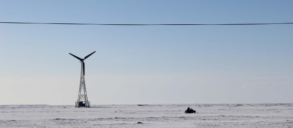 A snowmachine racing past one of Kwigillingok's wind turbines. Photo: Rachel Waldholz/APRN