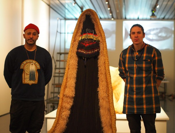 "Nicholas Galanin, left, with his collaborator Nep Sidhu standing beside a piece in the ""Kill The Indian, Save The Man"" exhibit. Photo: Zachariah Hughes."