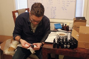 Steven Cornfield puts new labels on the new batch of beard oil. (Photo by Josh Edge/APRN)