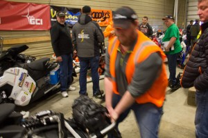Volunteers help move machines around in the garage. (Photo: Emily Russell/KNOM)