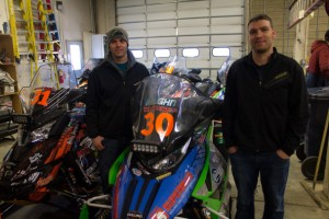 Iron Dog Team #30 Jerrod Vaughn and Geoff Crouse with their machines in the garage. (Photo: Emily Russell/KNOM)