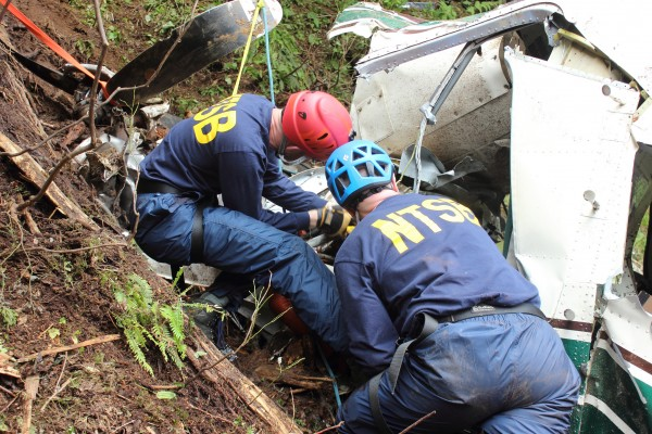 NTSB investigators Brice Banning and Clint Crookshanks on scene near Ketchikan examining the wreckage of a sightseeing plane that crashed in Alaska on June 25, 2015. This is not one of the crashes featured in the new TV series. (Creative Commons photo by National Transportation Safety Board)