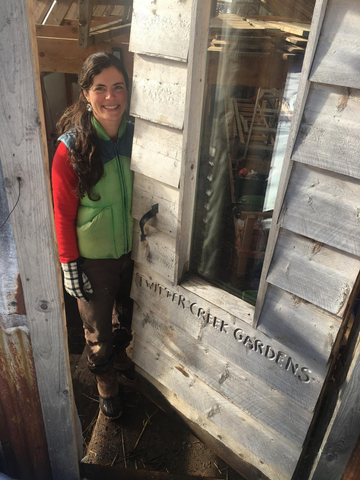 Emily Garrity peeks out from the door of her greenhouse at Twitter Creek Gardens on Ohlson Mountain outside Homer.( Photo by Daysha Eaton, KBBI - Homer)