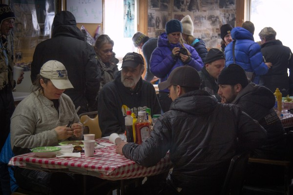 Jessie Royer, left, eats in Takotna with Mark Sass, Brent Sass's father, as well as Richie Diehl and Pete Kaiser. (Photo by Zachariah Hughes/ Alaska Public Media)