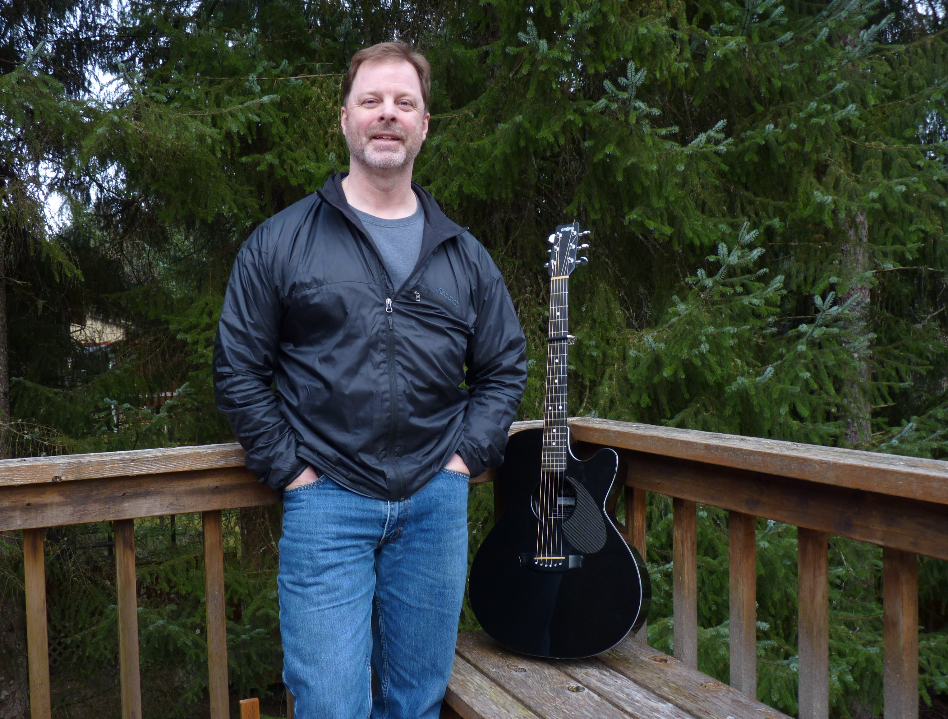 Juneau guitarist, singer and songwriter Kray Van Kirk poses on his back porch. He'll perform during the Alaska Folk Festival, April 4-11 in Juneau. (Photo by Ed Schoenfeld, CoastAlaska - Juneau)