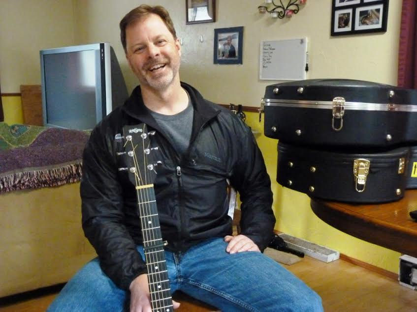 Juneau guitarist, singer and songwriter Kray Van Kirk talks about his music in his dining room, next to his guitar cases. He'll perform during the Alaska Folk Festival, April 4-11 in Juneau. (Photo by Ed Scheonfeld - CoastAlaska - Juneau)