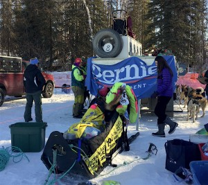 Monica Zappa displays a Bernie Sanders banner at the Iditarod restart in Willow. (Photo by Zach Hughes/KSKA.)