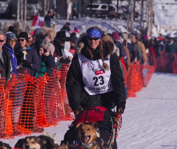 People crowd behind an orange gate to watch mushers and their sled dogs depart on a snow trail.