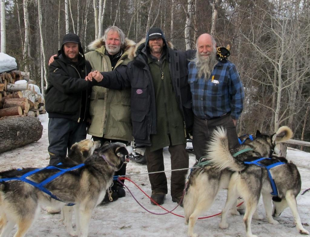 "Expedition members celebrate their success upon arrival in Eagle. Front row: ""the real heroes"" – the dogs that pulled the three sleds over the 700-mile journey. Back row, from left: Graham Burke, Tim Oakley, Wayne Hall and Earl Rolf, who broke trail and ferried supplies to caches along the route. (Photo courtesy of inamundsensfootsteps.com)"