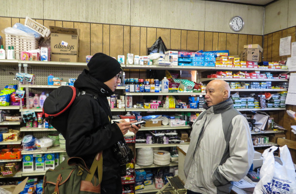 Brian Adams interviews Karl Ashenfelter at the White Mountain Native Store. (Photo by Laura Kraegel, KNOM - Nome)