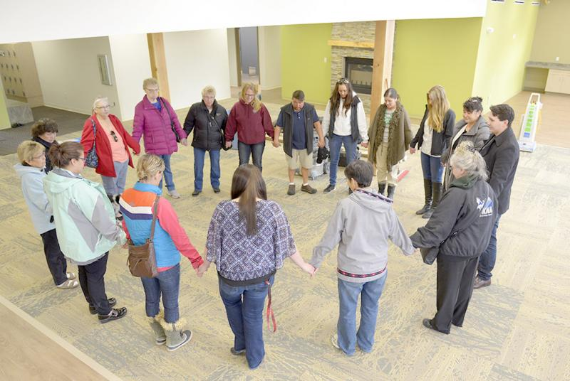 Sharon Isaak (bottom right, grey jacket) leads members of the Kenaitze Indian Tribe's Elders Committee in a closing prayer after the group toured for the first time the tribe's new Elders building on Feb. 11, 2016. (Photo courtesy of Scott Moon with the Kenaitize Indian Tribe)