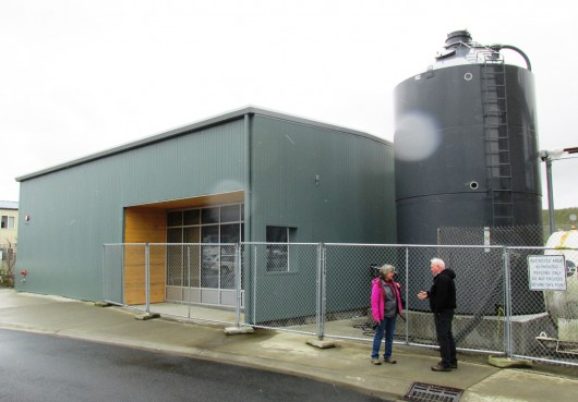 Karen Petersen and Mike Carney talk outside the Ketchikan International Airport's new biomass boiler building. The pellet silo on the right holds up to 30 tons. (Photo by Leila Kheiry, KRBD - Ketchikan)
