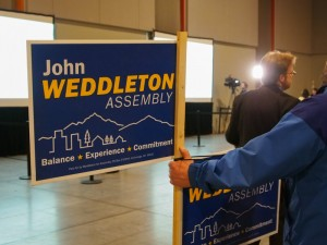 A John Weddleton supporter holding a sign shortly before the candidate was pronounced the winner in the South Anchorage race. (Photo by Zachariah Hughes/Alaska Public Media)