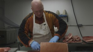 Joe Harvey cuts meat at the Point Mackenzie Correctional Farm. (Norris/Alaska Public Media)