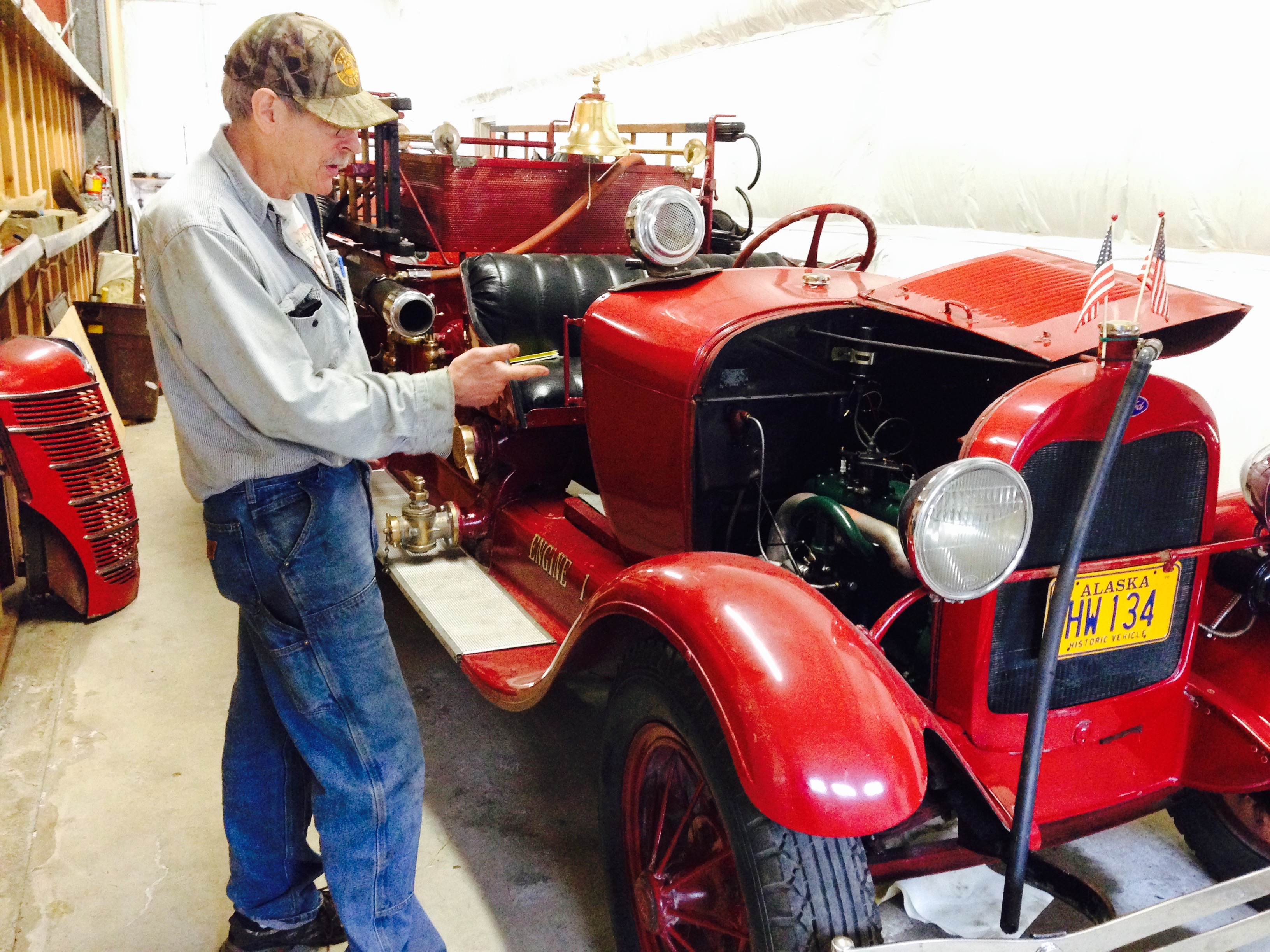 Jack Slaght points to the engine he overhauled in the 1928 Model A fire truck. (Photo by Angela Denning, KFSK - Petersburg)