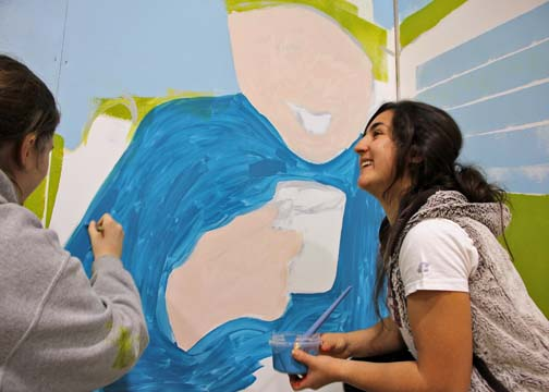 Logan Ball and Aubrey Romo of Aleknagik paint a base layer on Apayo Moore's mural, which will depict chuckling, storytelling elders with subsistence scenes in the background. (Photo by Hannah Colton/KDLG)