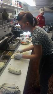 Mackenzie Moen assembles an order of the food truck's tacos. (Photo by Josh Edge/APRN)