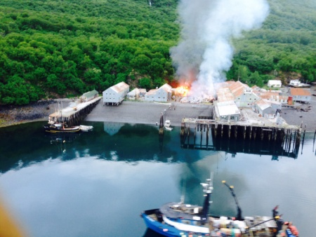 Responders assess a fire at the Park's Cannery near Uyak Bay on Kodiak Island, Alaska, June 2, 2016. The Coast Guard launched an MH-60 Jayhawk helicopter crew to assist with rescue efforts. (Photo courtesy of U.S. Coast Guard)