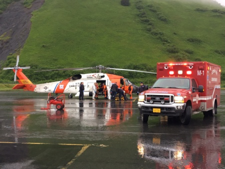The U.S. Coast Guard and emergency medical personnel transfer patients from a MH-60 Jayhawk helicopter to an ambulance in Kodiak, Alaska, June 2, 2016. The helicopter crew responded to a report of a fire at the Park's Cannery near Uyak Bay on Kodiak Island. (Courtesy photo by U.S. Coast Guard)