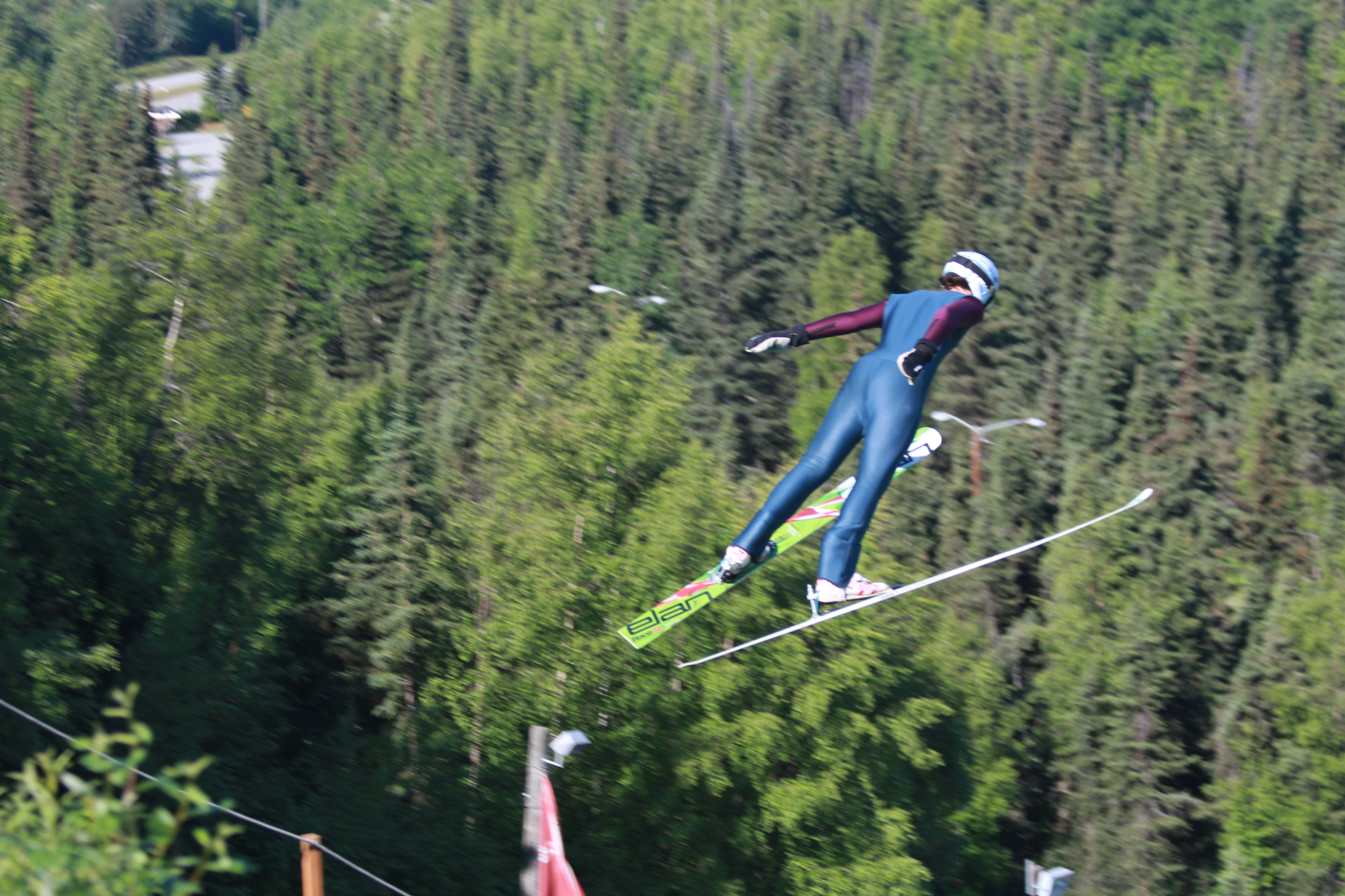 One of the young members of the Nordic Ski Association of Anchorage flies off of one of the new summer ski jumps. The Hilltop ski jump facility is the first of its kind to allow for ski jumping in the summer in Alaska. (Photo by Wesley Early, Alaska Public Media - Anchorage)