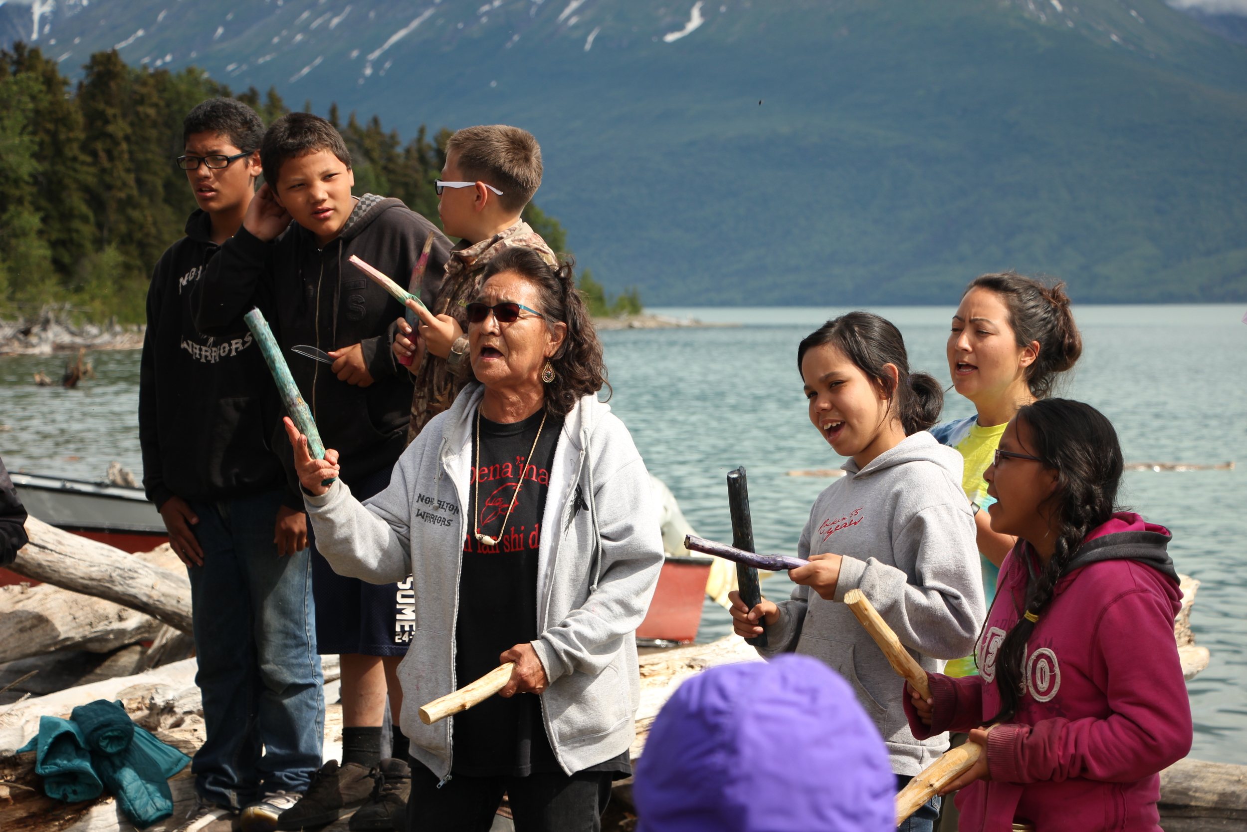 Michelle Ravenmoon (right), Nondalton elder Pauline Hobson (left) and kids sing a Dena'ina song at the end-of-camp potluck (Photo by Hannah Colton, KDLG - Dillingham)
