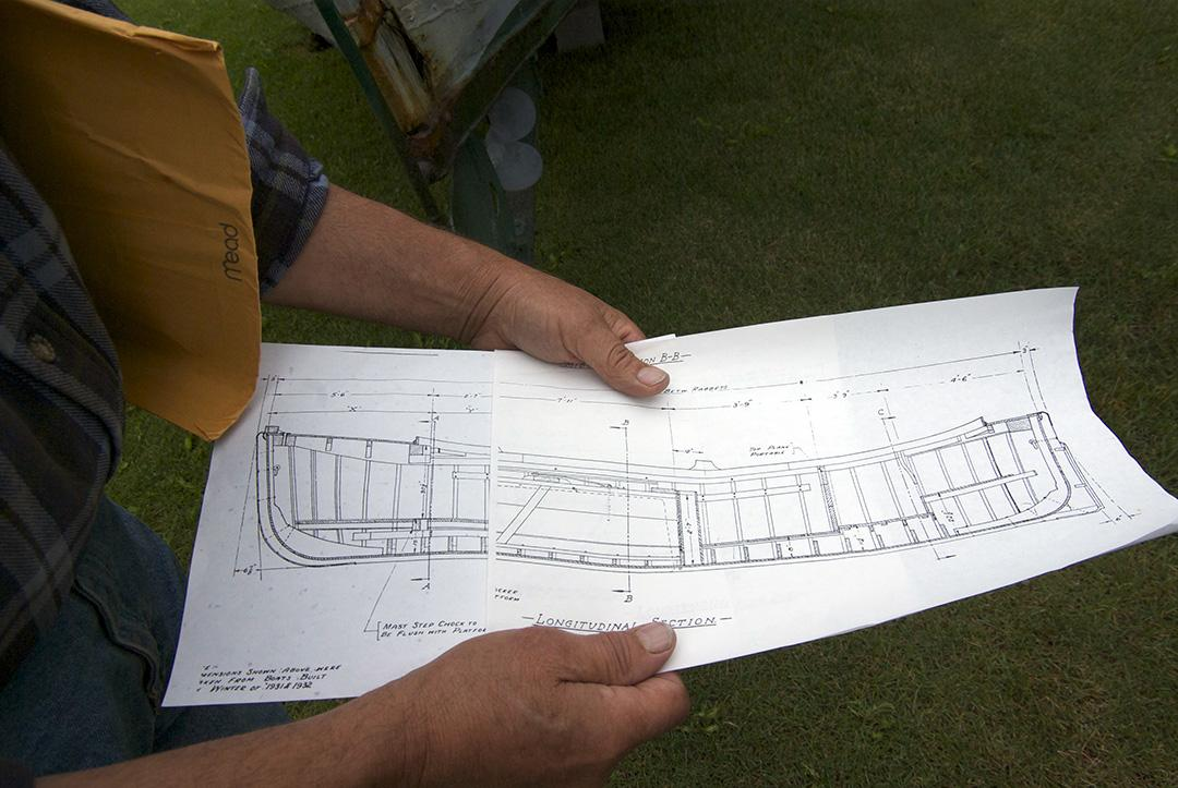 Johansen shows the plans for his dad's old boat, built in the winter of 1931-1932 in the Seattle area. (Photo by Jenny Neyman, KBBI - Homer)