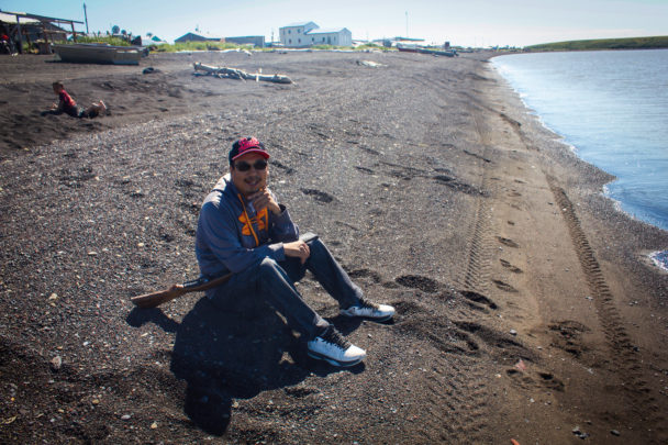 Bernard Abouchuk sits on the beach in Stebbins waiting for a seal. (Photo by Emily Russell, KNOM - Nome)