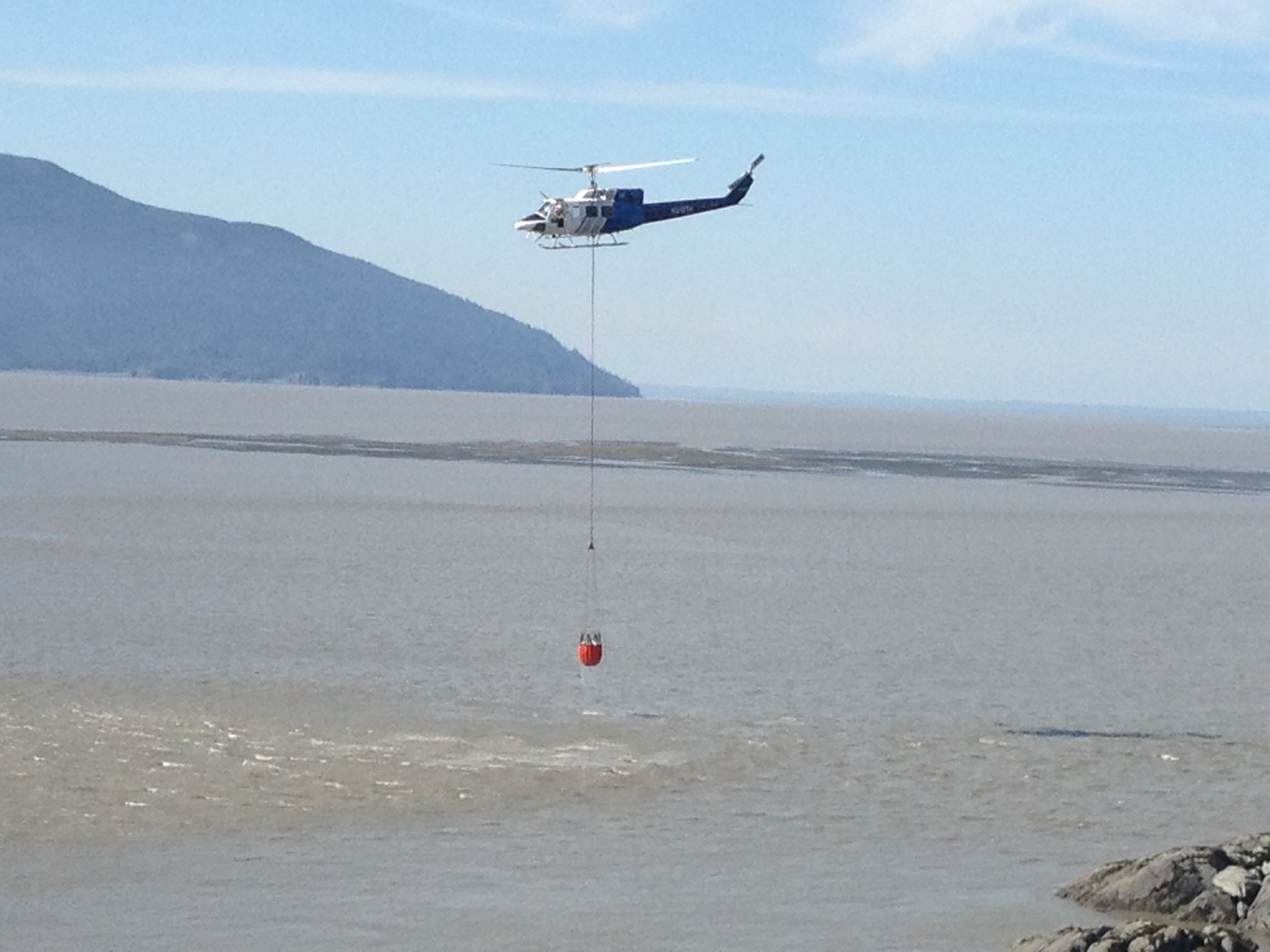 Forestry helicopter dips bucket into Turnagain arm while fighting the McHugh Creek wildfire on Sunday. (Photo by Ellen Lockyer, Alaska Public Media - Anchorage)