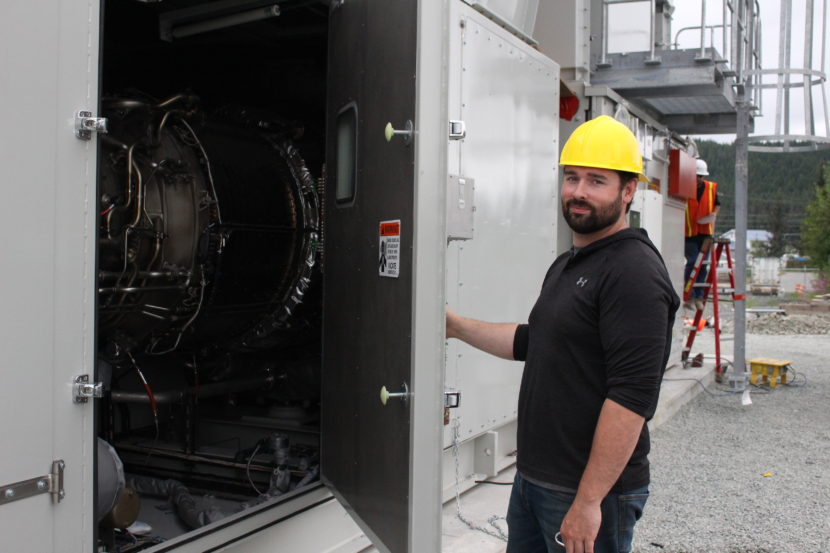 Bryan Farrell, an engineer at AEL&P, holds open the hatch to the diesel turbine. (Photo by Elizabeth Jenkins, KTOO - Juneau)