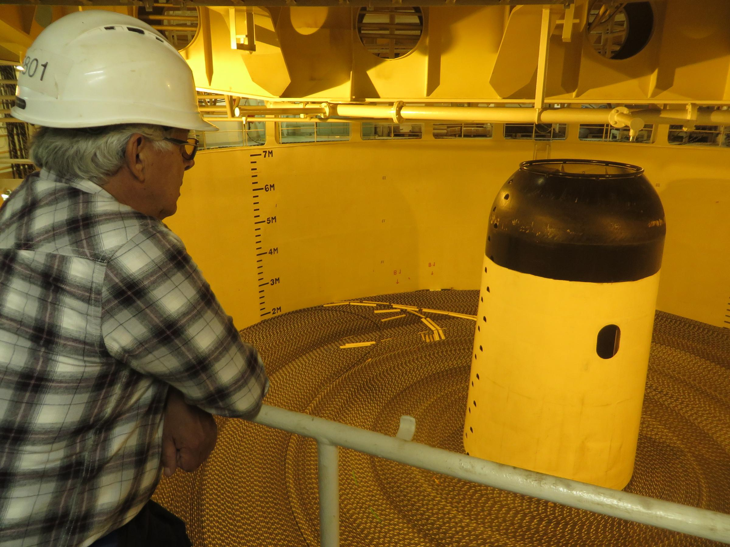 Reggie Joule looks over tanks of coiled fiber optic cable in the Ile de Brehat. (Photo by Laura Kraegel, KUCB - Unalaska)