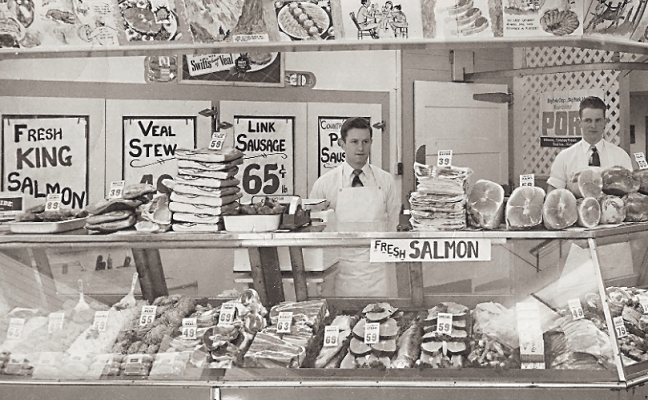 Bill Cope (right) and a butcher shop employee pose in 20th Century Market in downtown Juneau around 1950. (Photo courtesy of Violet Cope and featured on cover of Alaska Economic Trends, July 26, Volume 36 number 7.)