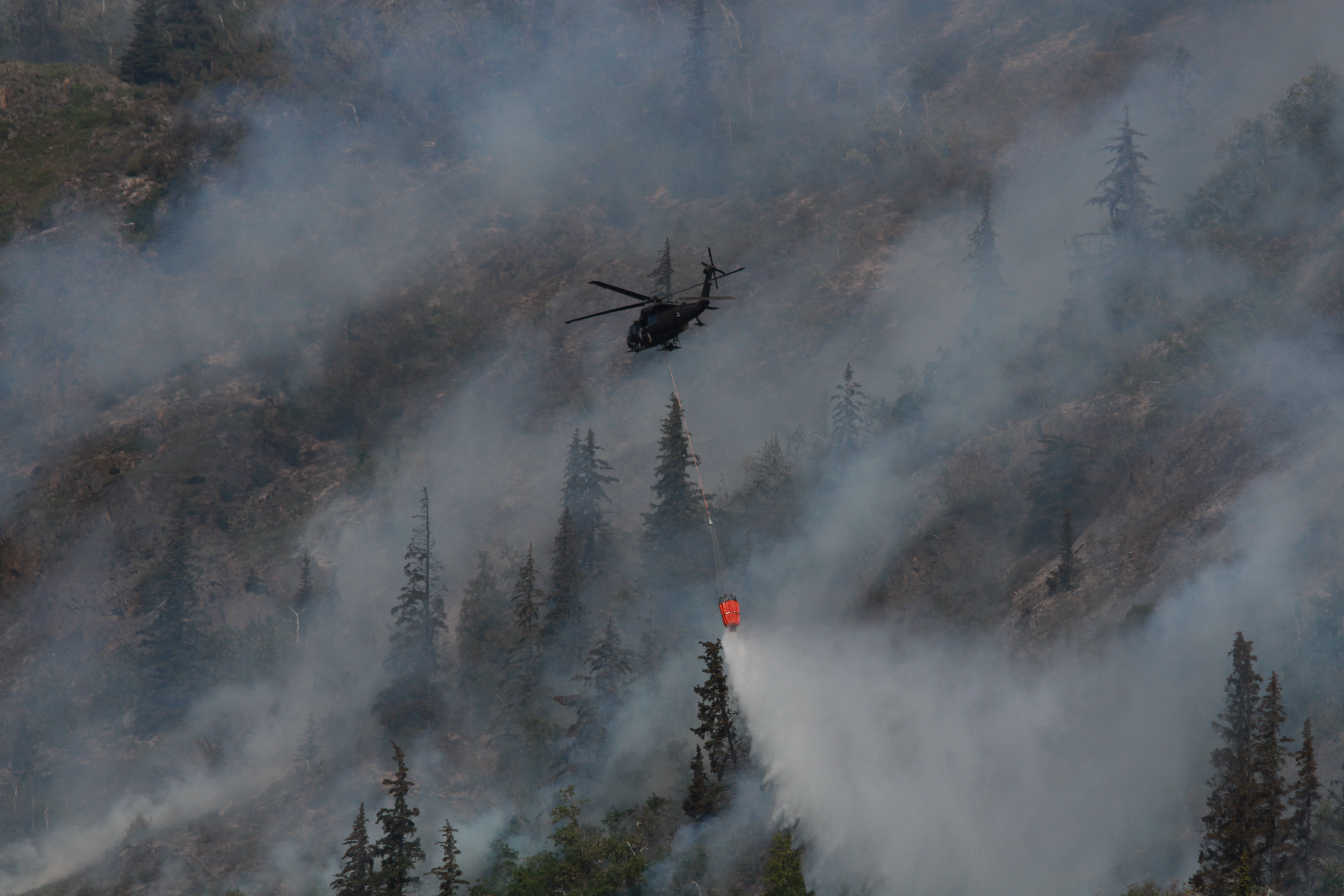 "A helicopter dumps water from a ""Bambi Bucket"" to fight the McHugh fire. (Photo by Wesley Early, Alaska Public Media - Anchorage)"