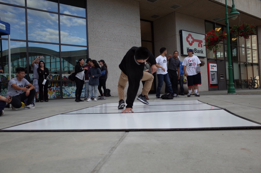 Ives Viray, one of the breakdancers with Anchorage Artist Co-Op, demonstrates his skills in downtown Anchorage)