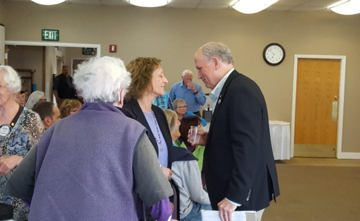 Governor Bill Walker greets Carol Swartz, Director of Kachemak Bay Campus-Kenai Peninsula College, University of Alaska Anchorage at the joint meeting of Homer's two Rotary clubs at Lands End Resort in Homer on Tuesday, August 2. (Shahla Farzan, KBBI - Homer)