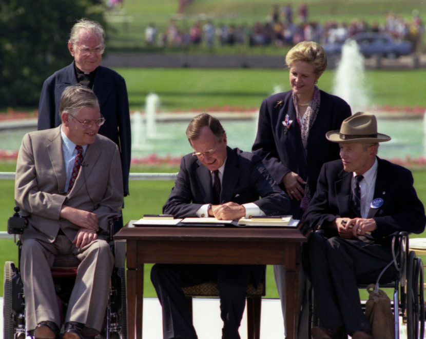 P14777-18  President Bush signs the Americans with Disabilities Act on the South Lawn of the White House.  Sharing the dais with the President and he signs the Act are (standing left to right):  Rev. Harold Wilkie of Clairmont, California; Sandra Parrino, National Council on Disability; (seated left to right):  Evan Kemp, Chairman, Equal Opportunity Commission; and Justin Dart, Presidential Commission on Employment of People with Disabilities.  Mrs. Bush and Vice President Quayle participate in the Ceremony. 26 July 1990 (Photo courtesy of George Bush Presidential Library and Museum)