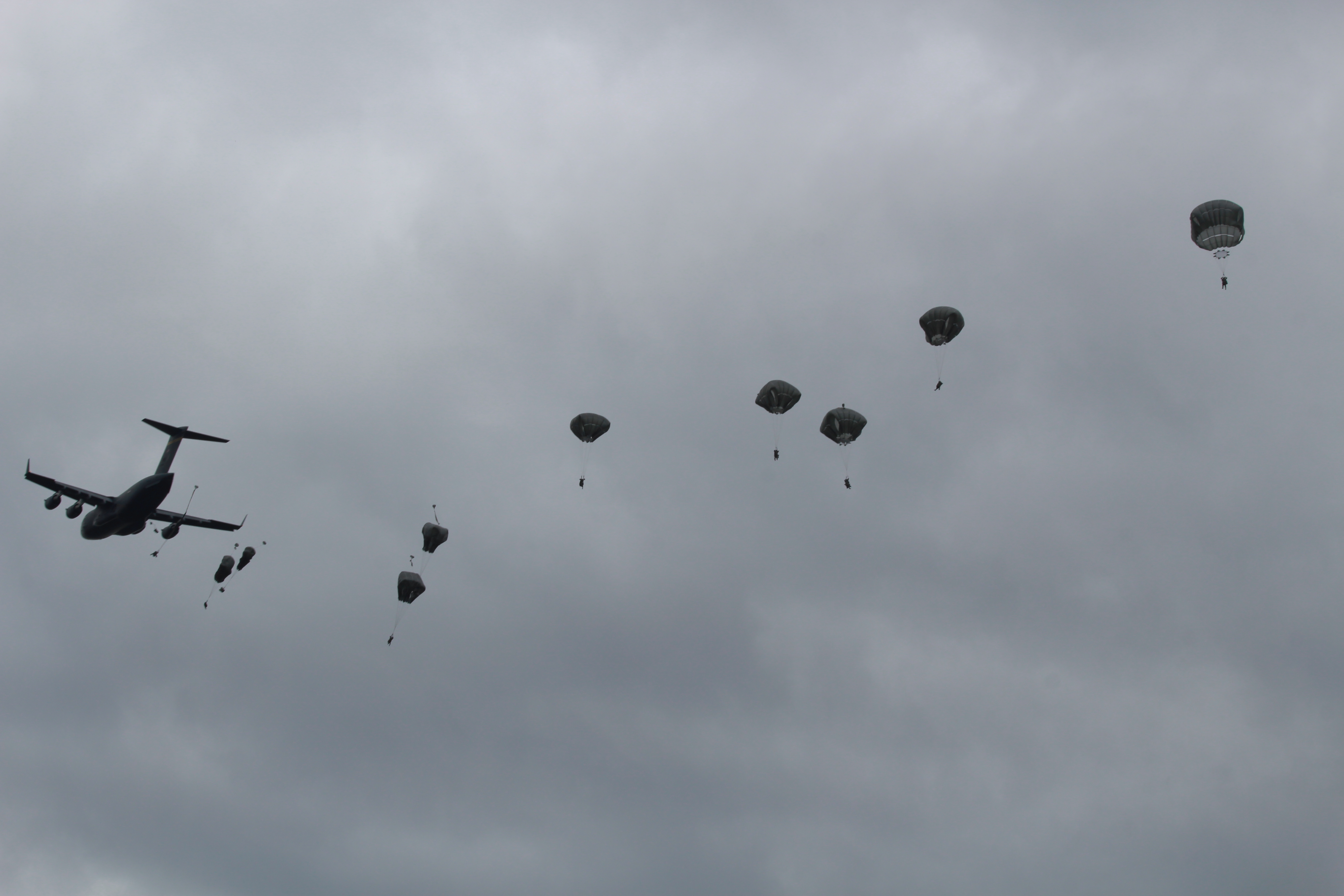 Paratroopers fall out of a C-17 and float to the ground (Photo by Wesley Early, Alaska Public Media - Anchorage)