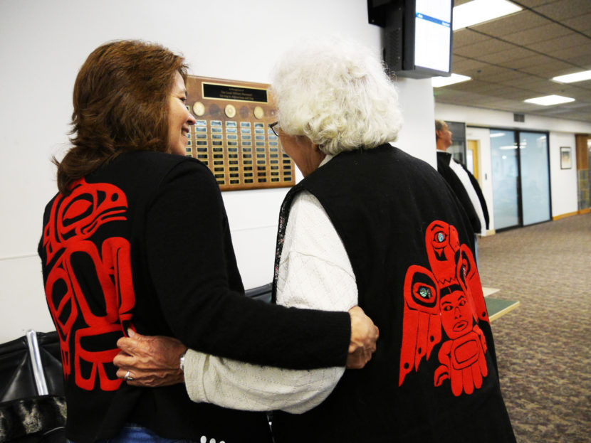Valerie Hillman shows off her clan's crest, the T'akdeintaan's Raven, while holding arms with Hoonah tribal elder Lillian Austin, who's clan crest is the Shangukeidí's Thunderbird. The women were on standby to go to Gustavus at Juneau International Airport on Thursday. (Photo by Lakeidra Chavis, KTOO - Juneau)