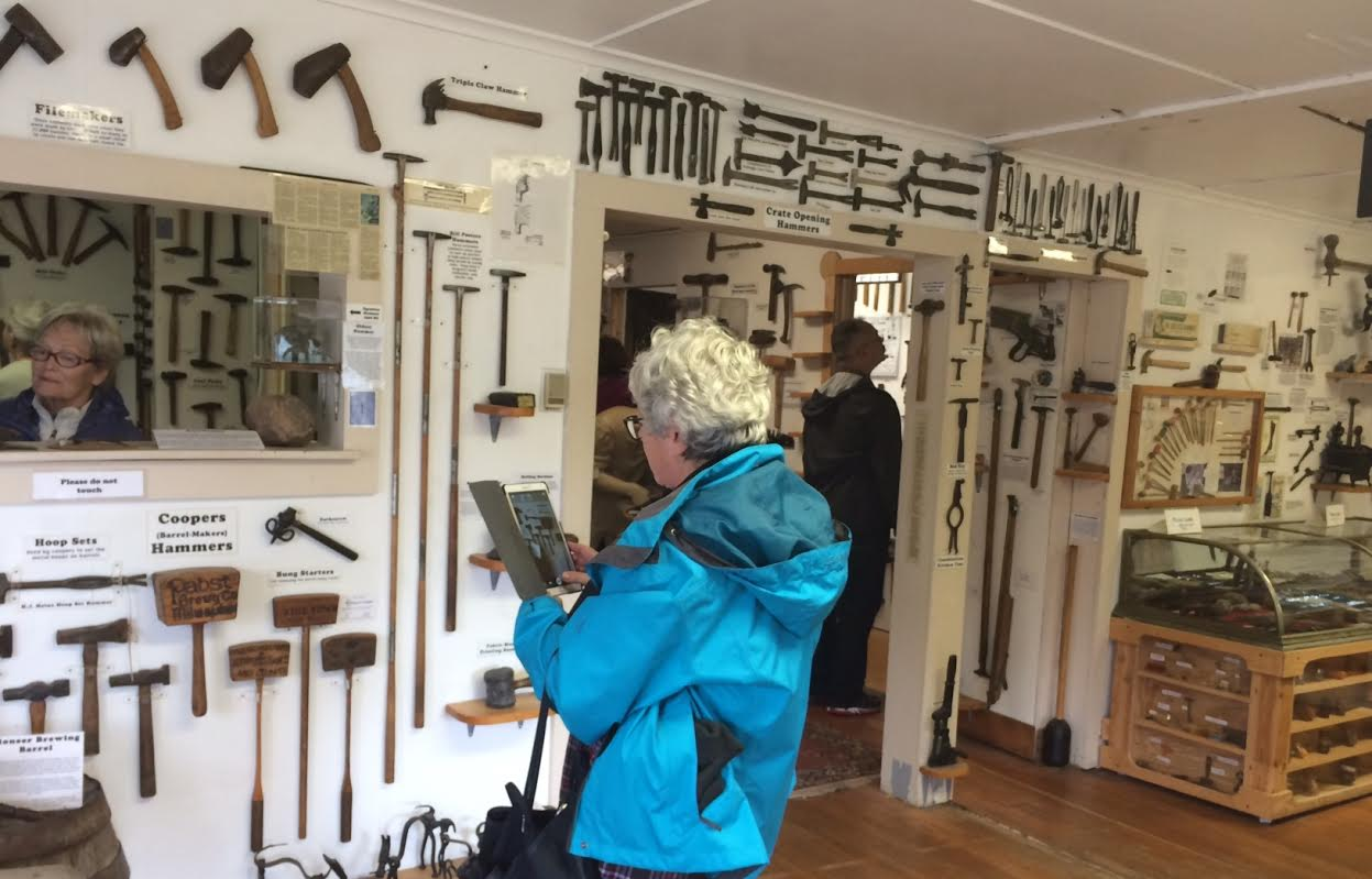 A cruise ship guest snaps photos of the extensive hammer collection at the Hammer Museum in Haines on Wednesday, Aug. 10, 2016. Wednesdays are the museum's busiest day. (Photo by Jillian Rogers, KHNS - Haines)
