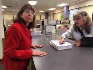 Margaret Stock, left, turns in nominating signatures. Clerk Deborah Moody-Herrera accepted them. Next they'll be sent to Juneau for verification. Photo: Liz Ruskin/Alaska Public Media