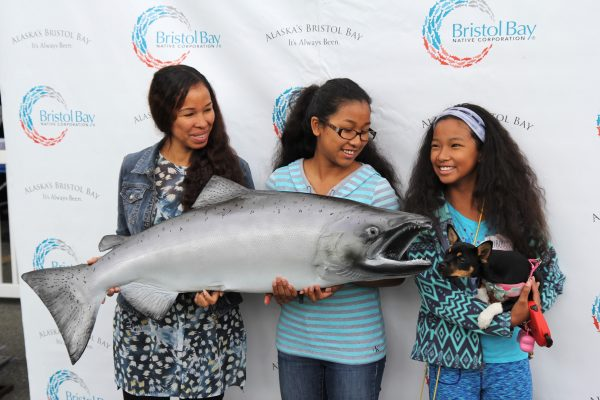 (Left to right) Danya Nickita, Mariah Kiljoha and Isis Kiljoha pose for a photo at a community cookout hosted by the Bristol Bay Native Corporation celebrating Salmon Day in Anchorage on August 10. (Photo by Graelyn Brashear - KSKA/Anchorage)