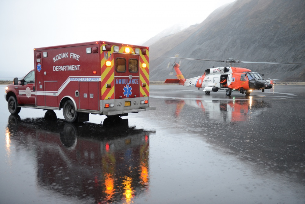 A Coast Guard Air Station Kodiak, Alaska, MH-60 Jayhawk helicopter crew transfers a patient to an ambulance in Kodiak after a medevac from a fishing boat in February 2016. (U.S. Coast Guard photo by Petty Officer 3rd Class Lauren Steenson)