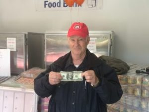 Jim Wilcox holds up a $100 donation on Saturday. (Photo by Quinton Chandler, KTOO - Juneau)
