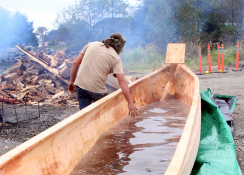 Tommy Joseph feels the warm water after the batch of lava rocks are taken out. (Photo by Emily Russell - KCAW - Sitka)