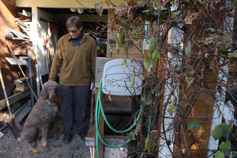 Bob Deering at his home with his dog and compost bins. (Photo by Elizabeth Jenkins, Alaska's Energy Desk - Juneau)