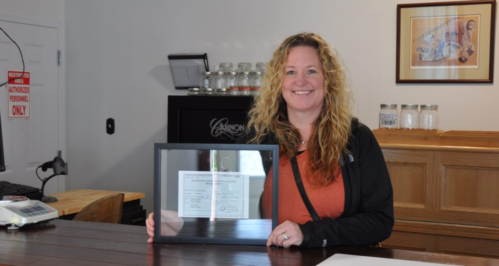 Tara Bass with in the Remedy Shoppe with her license to open (Photo courtesy of Tara Bass)