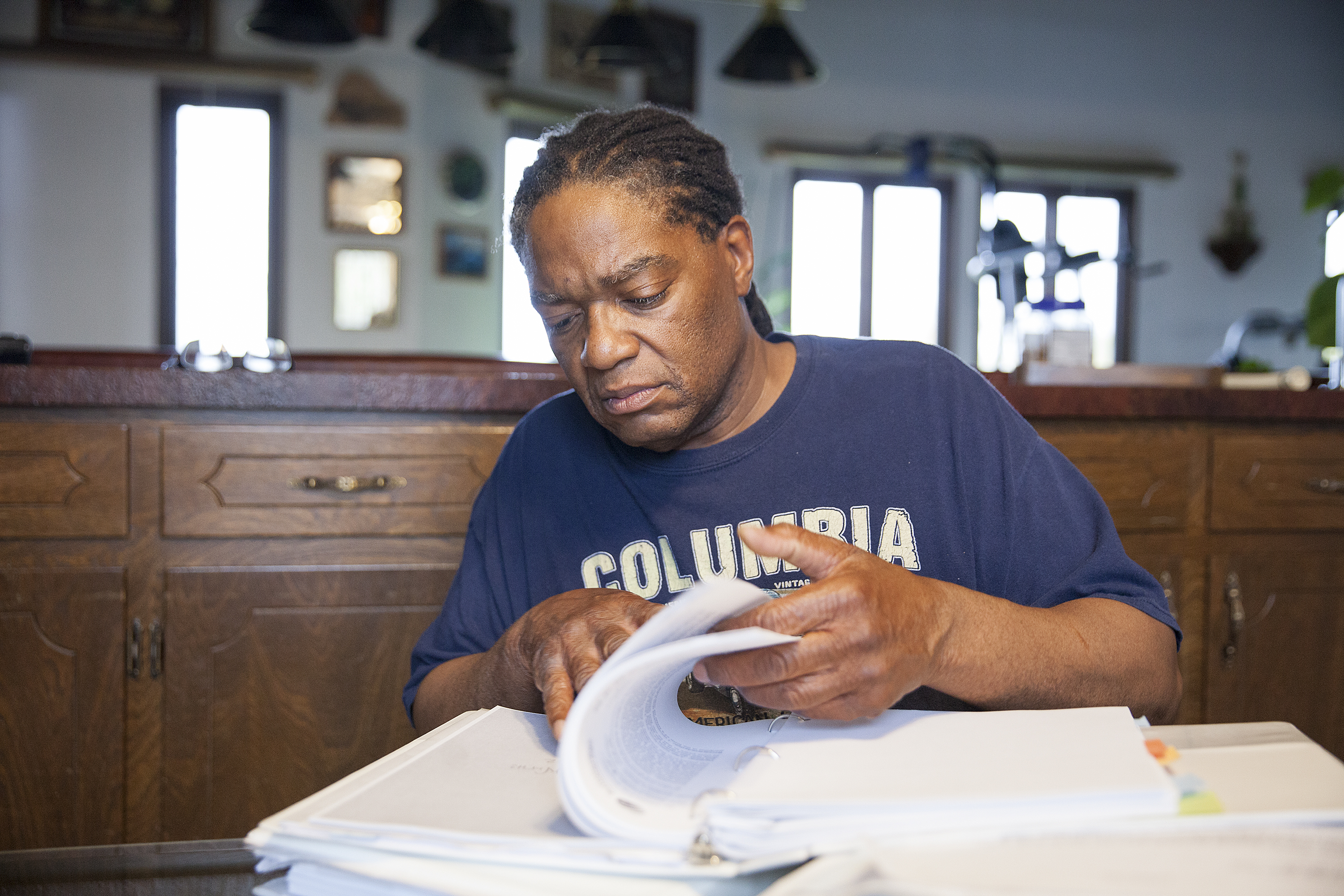 """Theodore """"Teddy"""" Burns looks through documents from his discrimination case at his home in Anchorage. Burns' appeal with the Alaska Ombudsman's office took eight years to complete. (Photo by Rashah McChesney, KTOO - Juneau)"""