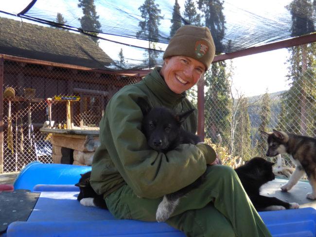Jennifer Raffaeli plays with the kennel's newest members. (Zoë Sobel, Alaska's Energy Desk - Unalaska)