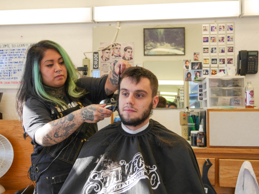 Eva Carrillo cuts Kyle White's hair at Gerry's Barbershop. Kyle has been going to the shop since he was a kid. (Photo by Lakeidra Chavis, KTOO - Juneau)