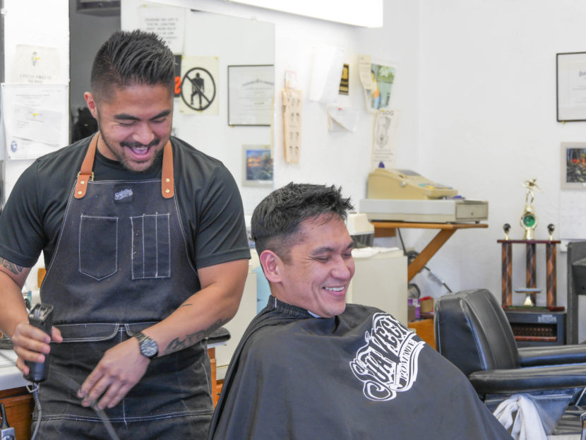 Gerry Carrillo Jr. cuts David Mende's hair. Gerry is the newest family member to work at Gerry's Barbershop. (Photo by Lakeidra Chavis, KTOO - Juneau)