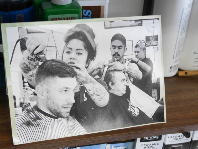 A photo of the Carrillo family sits on a shelf inside Gerry's Barbershop. From left to right: Eva, Gerry Jr., and Gerry Sr. (Photo by Lakeidra Chavis, KTOO - Juneau)